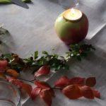 Vacker bordsdekoration med äpplen som värmeljushållare.